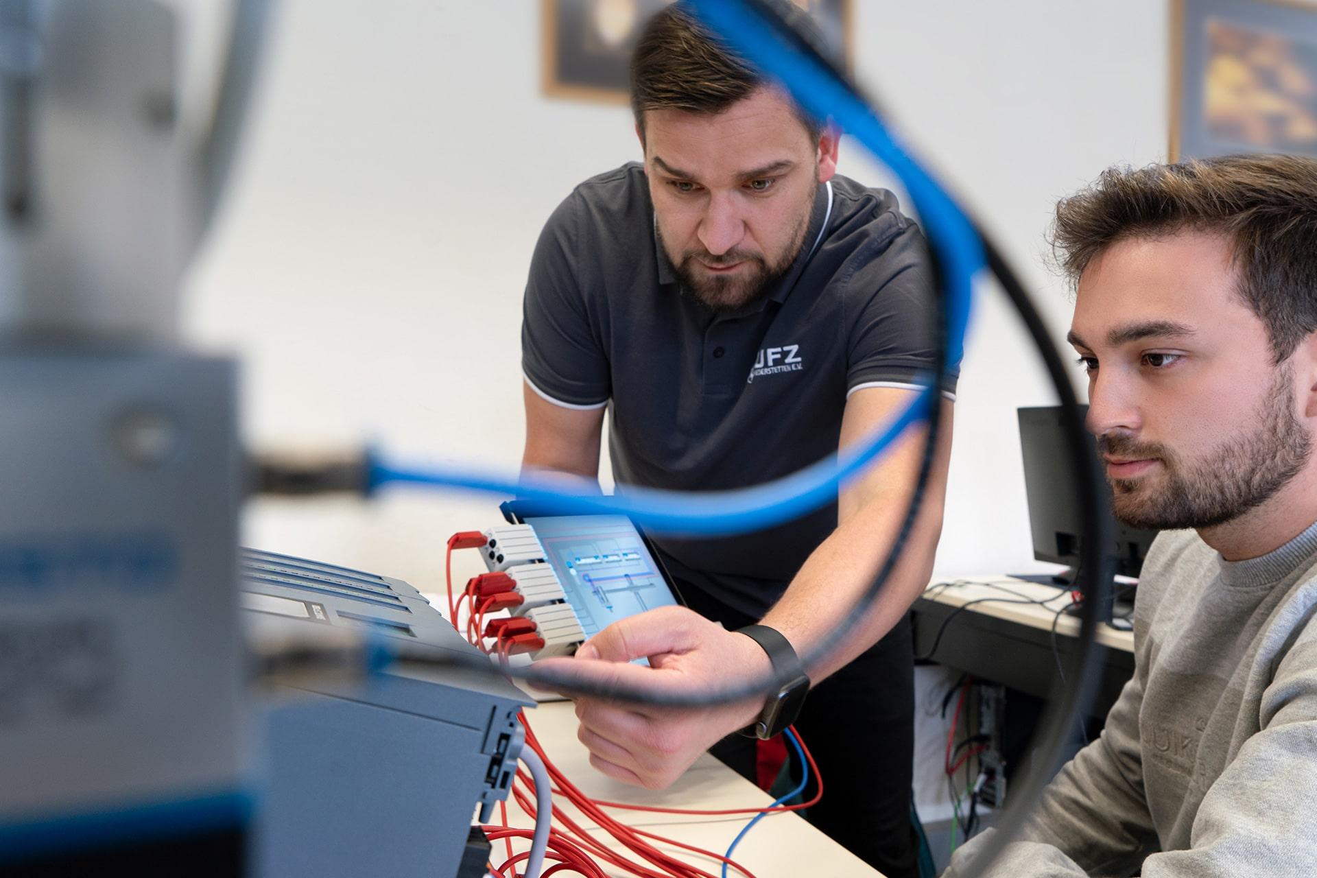 Umschulungszentrum UFZ in Niederstetten / Ausbilder erklärt einen elektrischen Aufbau